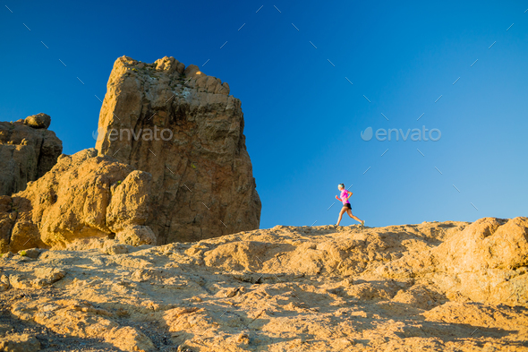 Woman running on rocky mountains, training and working out - Stock Photo - Images