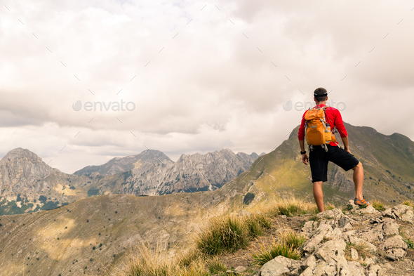 Hiking man or trail runner in mountains - Stock Photo - Images