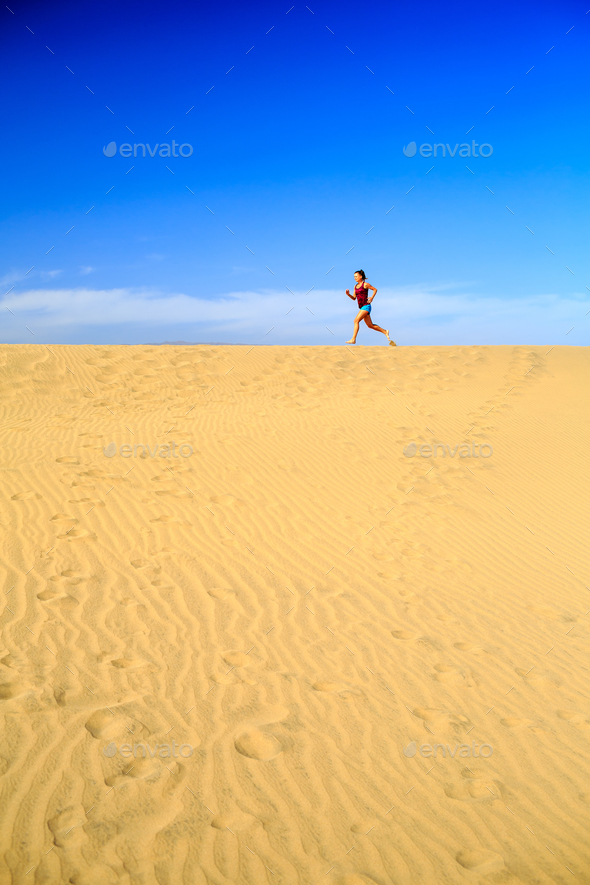 Young woman running on sand desert dunes - Stock Photo - Images