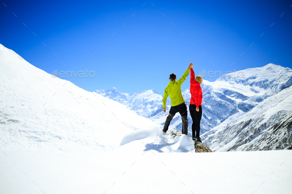 Couple hiking man and woman success in winter mountains - Stock Photo - Images