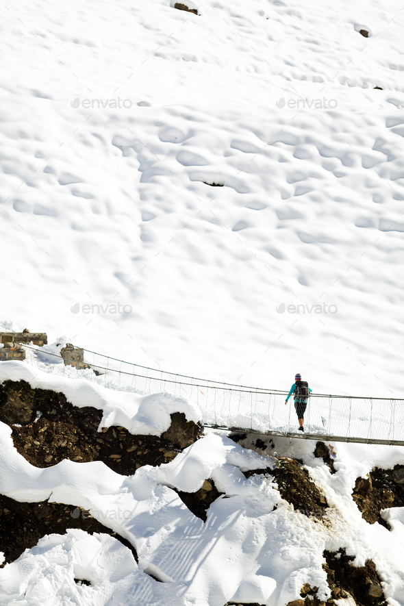 Woman walking on bridge in winter mountains - Stock Photo - Images