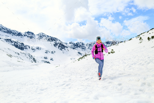 Woman running in mountains in inspirational winter landscape - Stock Photo - Images