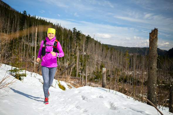 Woman winter trail running in mountains on snow - Stock Photo - Images