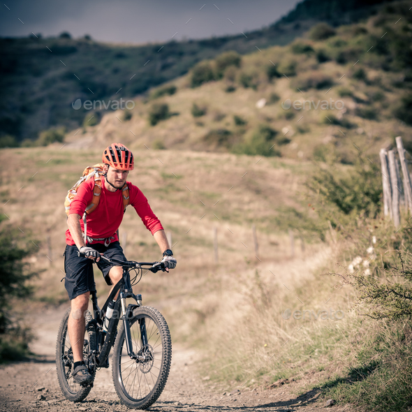 Mountain bike rider on country road, track trail in inspirationa - Stock Photo - Images