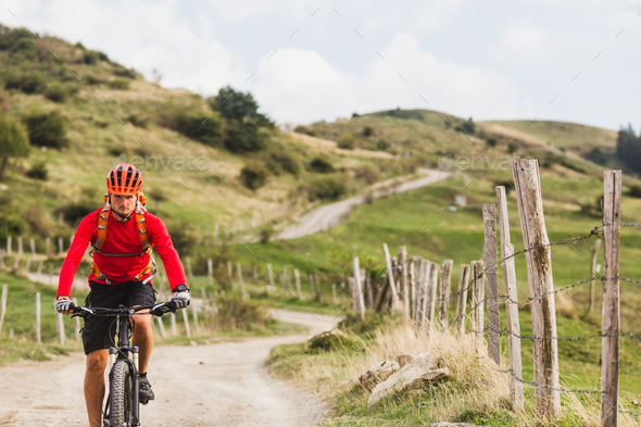 Man riding mountain bike on country road - Stock Photo - Images