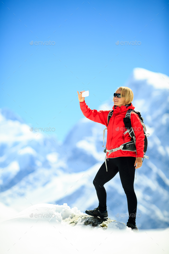 Woman doing smartphone selfie in mountains - Stock Photo - Images