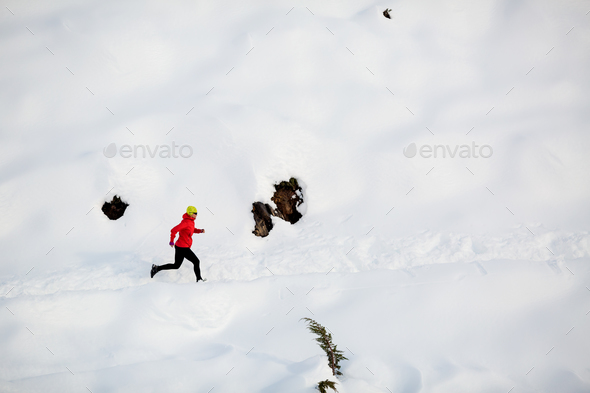Woman running in winter mountains - Stock Photo - Images
