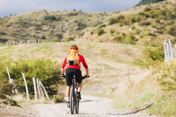 Man enduro mountain biking on country road - Stock Photo - Images