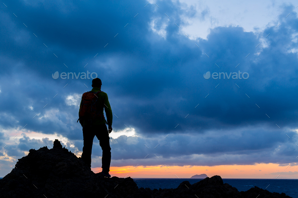 Hiking silhouette backpacker, inspirational sunset landscape - Stock Photo - Images