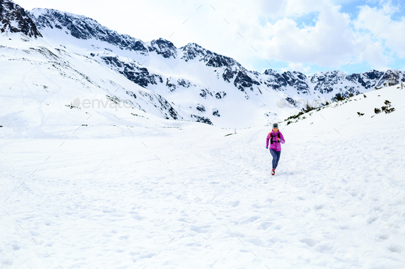 Happy woman running in mountains on winter sunny day - Stock Photo - Images