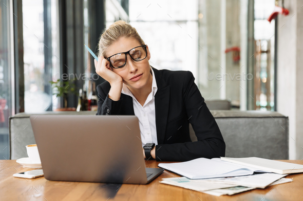 Tired blonde business woman sitting by the table in cafe - Stock Photo - Images