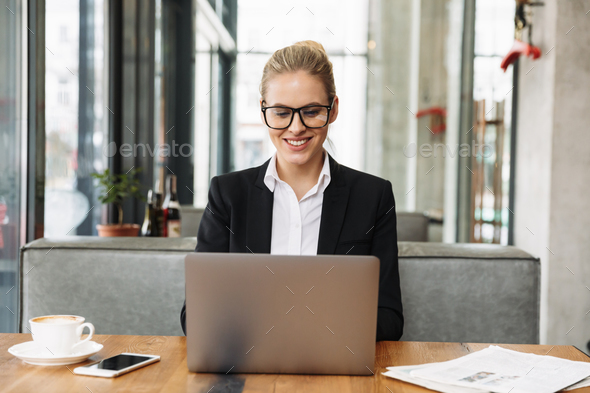 Smiling blonde business woman sitting by the table in cafe - Stock Photo - Images