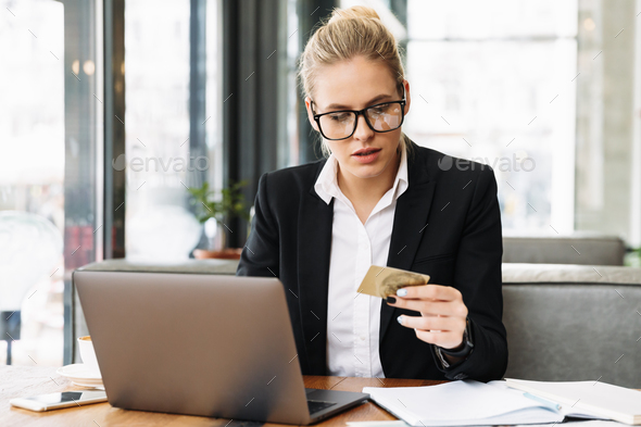 Concentrated blonde business woman sitting by the table in cafe - Stock Photo - Images