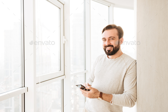Photo of candid brunette guy 30s in white shirt, spending time n - Stock Photo - Images