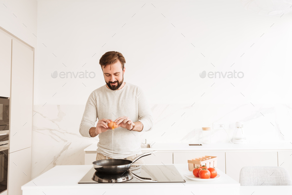 Photo of european man with short brown hair and beard cooking om - Stock Photo - Images