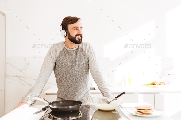 Portrait of a smiling young man cooking pancakes - Stock Photo - Images
