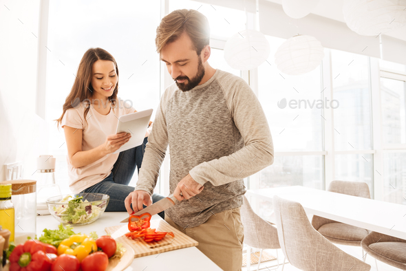 Portrait of a smiling young couple cooking - Stock Photo - Images