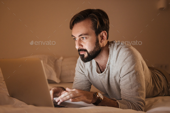 Portrait of a concentrated man using laptop computer - Stock Photo - Images