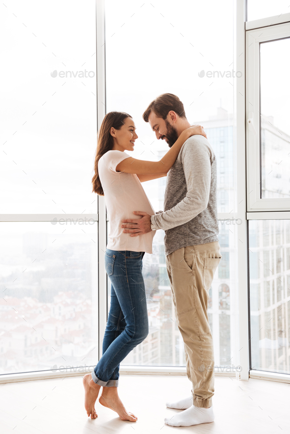 Pretty pregnant young couple hugging - Stock Photo - Images