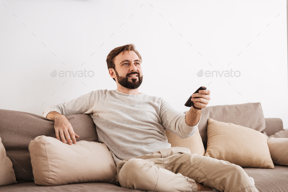 Portrait of a smiling man holding remote control - Stock Photo - Images