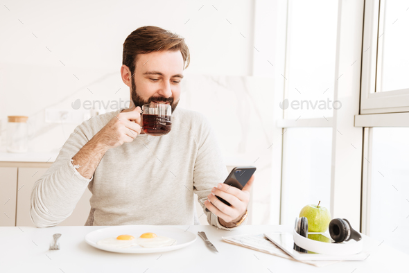 Bearded man in casual shirt drinking tea and using smart phone, - Stock Photo - Images