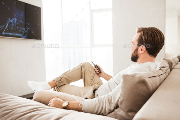 Photo of relaxed adult man 30s in casual clothing sitting on sof - Stock Photo - Images