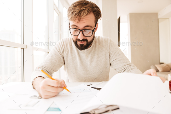 Portrait of a busy man working with documents - Stock Photo - Images