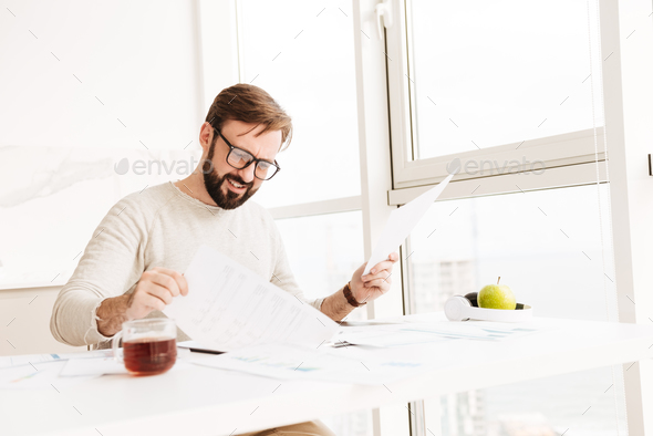 Portrait of a disappointed man working with documents - Stock Photo - Images
