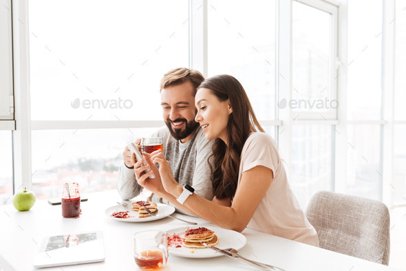 Happy young couple having breakfast - Stock Photo - Images