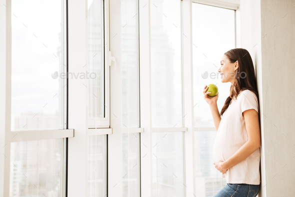 Smiling pregnant young woman eating green apple - Stock Photo - Images