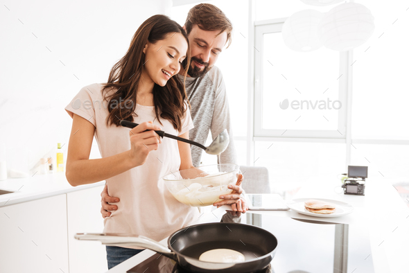 Portrait of a happy young couple cooking pancakes - Stock Photo - Images