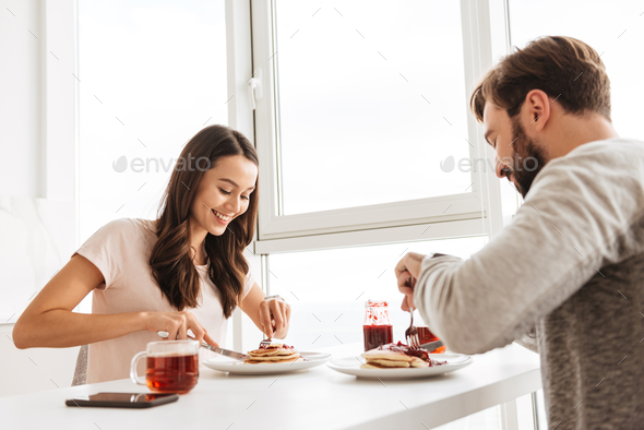 Beautiful young couple having breakfast while sitting together - Stock Photo - Images