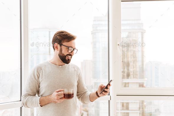 Portrait of a smiling man using mobile phone - Stock Photo - Images