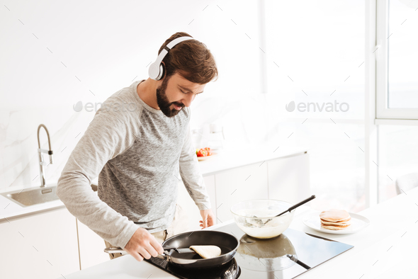 Portrait of a concentrated young man cooking pancakes - Stock Photo - Images