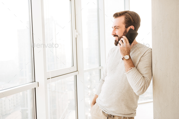 Sociable guy with beard and mustache looking through big window - Stock Photo - Images