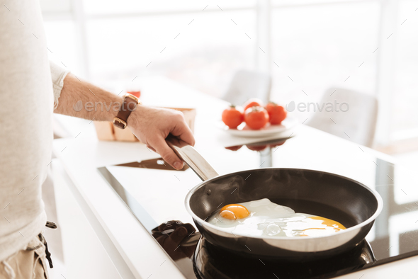 Cropped photo of caucasian bachelor in white shirt cooking omele - Stock Photo - Images