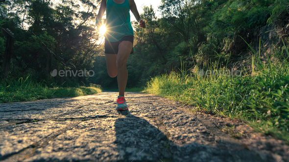 Trail running on sunrise forest trail - Stock Photo - Images