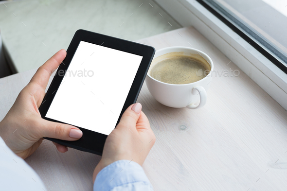 Young woman sitting by the window with an e-book - Stock Photo - Images