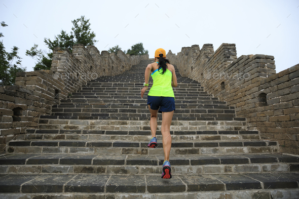 Woman running upstairs on great wall in China - Stock Photo - Images