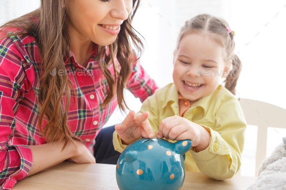 Child girl putting coin to piggy bank - Stock Photo - Images