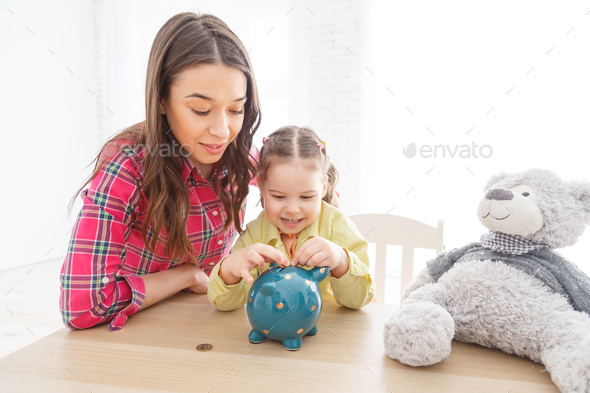 Mother and daughter putting coins into piggy bank - Stock Photo - Images