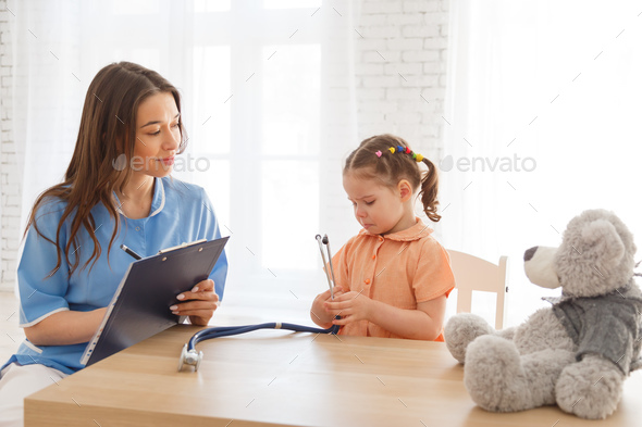 Child girl at the reception of a pediatrician. - Stock Photo - Images