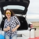 Happy Young Woman on Summer Travel Vacation Sitting in a Car Trunk - VideoHive Item for Sale