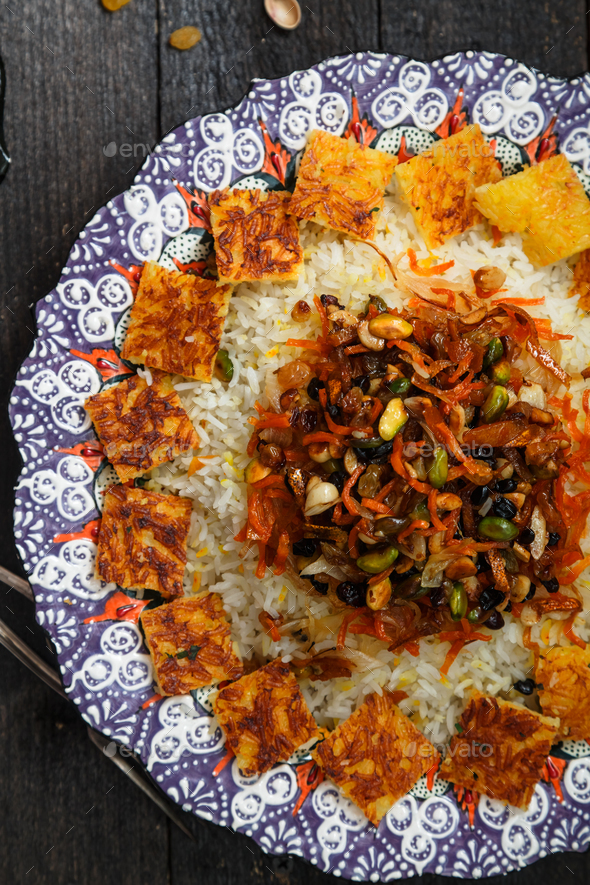 Iranian jewelled rice topped with orange zest, nuts and raisins in traditional plate - Stock Photo - Images