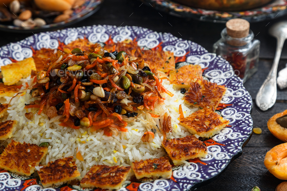Iranian wedding pilaf topped with nuts, orange zest and raisins, rustic style - Stock Photo - Images