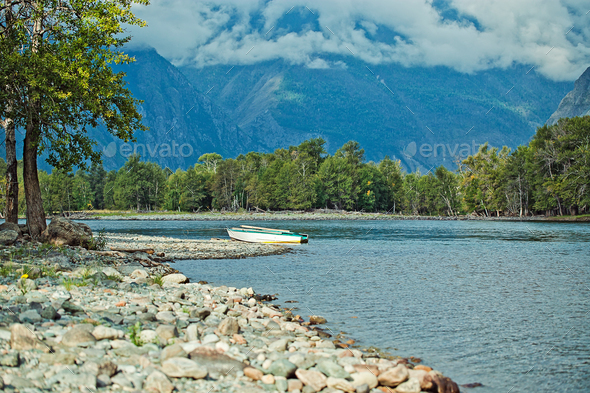 Lone boat sitting on the shore of a river Chulyshman, Akkurum, Altai, Russia - Stock Photo - Images