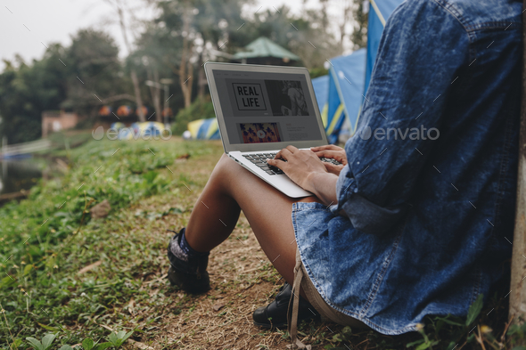Woman alone in nature using a laptop on a camp site getaway from work or internet addiction concept - Stock Photo - Images