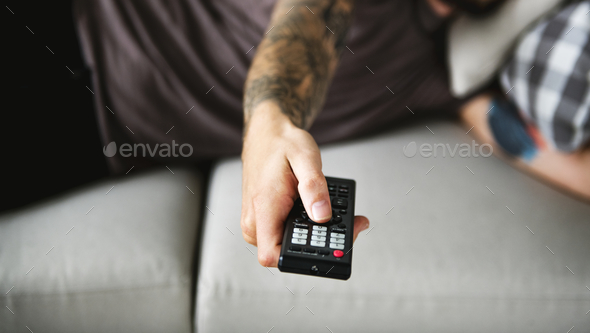 Man lying on a couch watching tv - Stock Photo - Images