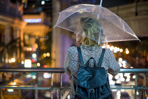 Blond woman taking cover under her umbrella - Stock Photo - Images