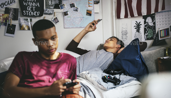 Teenage boys hanging out in a bedroom playing a video game and using a smartphone - Stock Photo - Images